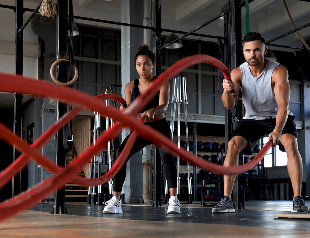 man and woman training in a gym with ropes