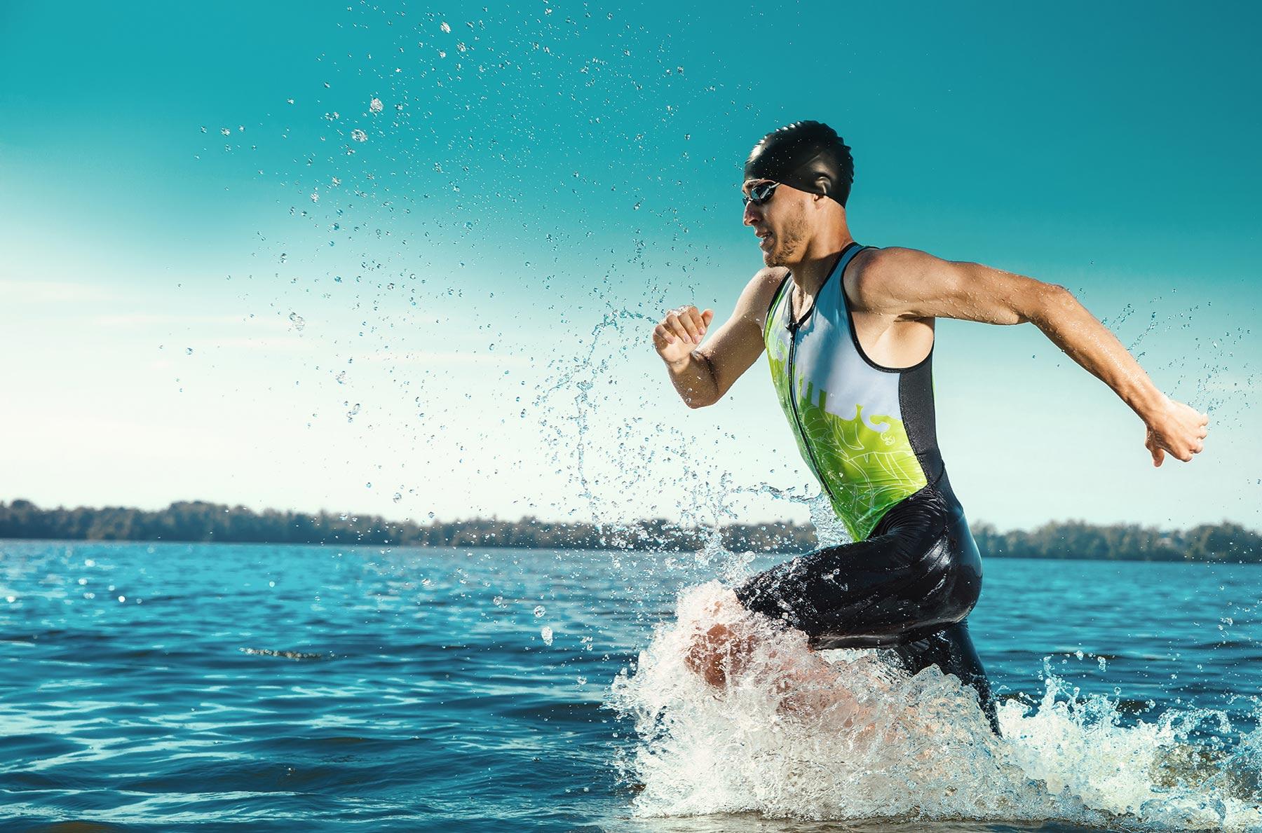 man swimmer running through the water in a triathlon
