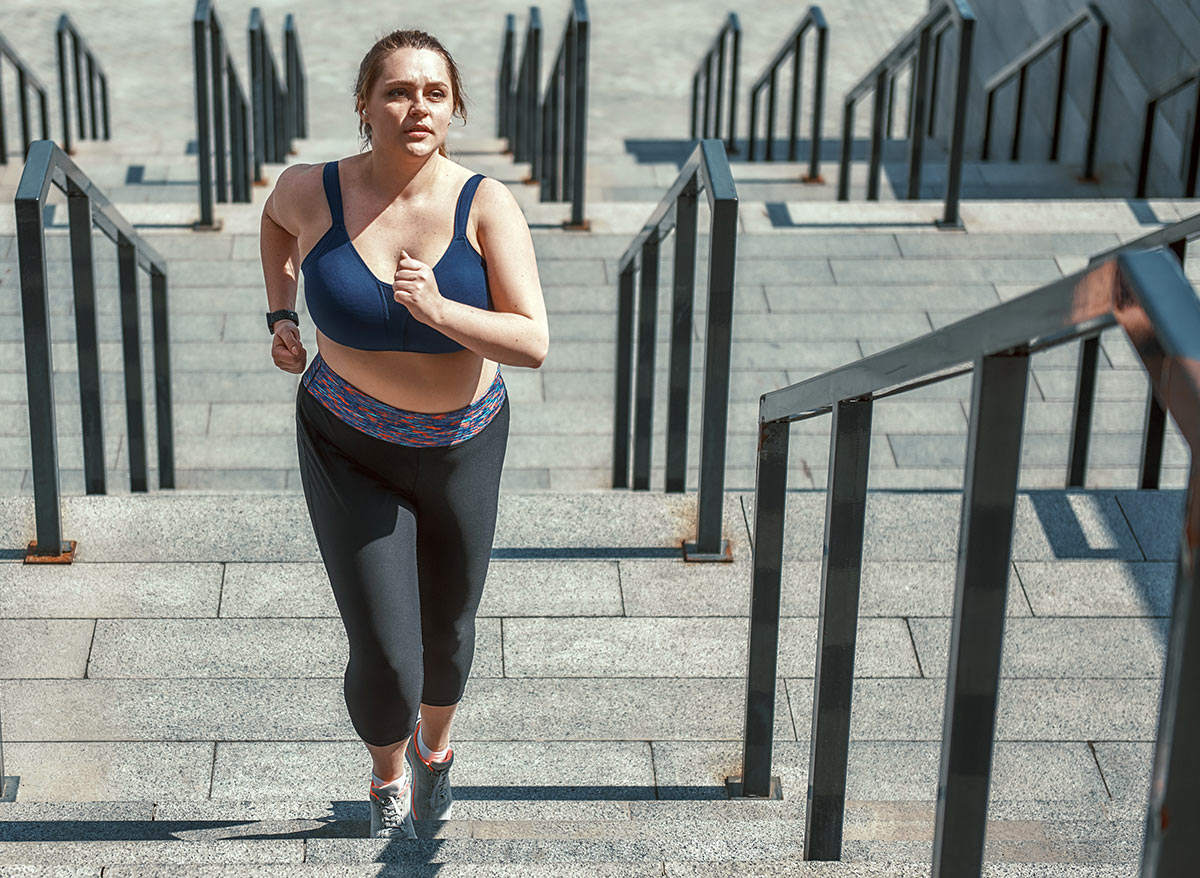 athletic woman running up a staircase
