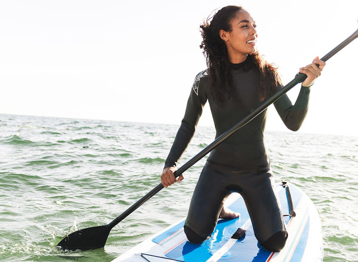 woman kneeling on a paddle board